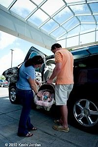 Man and Woman Loading Baby into a Car
